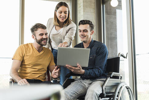 Young businessman in wheelchair showing laptop to colleagues in office - UUF19887