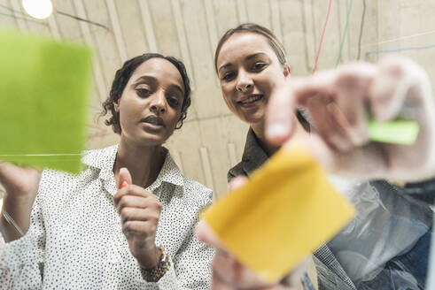 Two young businesswomen working on adhesive notes on glass table - UUF19896