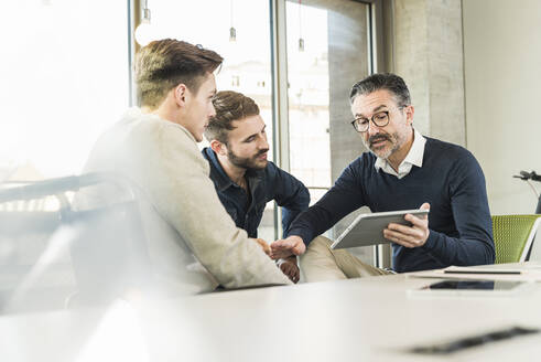 Three businessmen having a meeting in office sharing a tablet - UUF19941