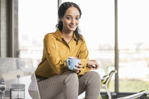 Portrait of smiling young businesswoman sitting on desk in office having a coffee break - UUF19968