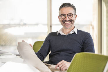 Portrait of a smiling mature businessman sitting at desk in office - UUF19998