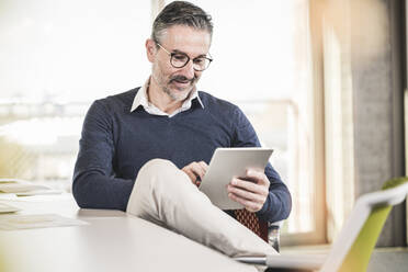 Mature businessman sitting at desk in office using tablet - UUF20001