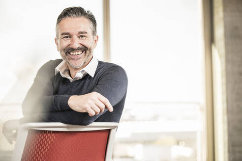 Portrait of a happy mature businessman sitting on chair in office - UUF20007