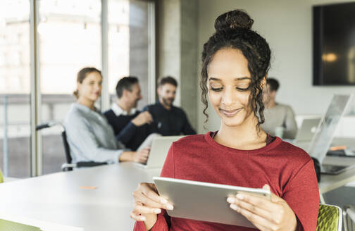 Smiling young businesswoman using tablet during a meeting in office - UUF20019