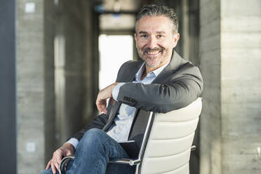 Portrait of a smiling mature businessman sitting on chair in office - UUF20043