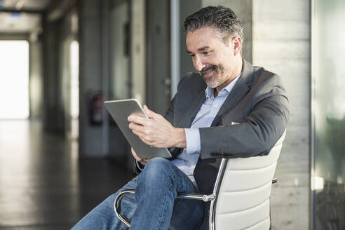 Mature businessman sitting on chair in office using tablet - UUF20046