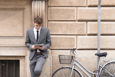 Young businessman leaning at facade looking at digital tablet - FMOF00851