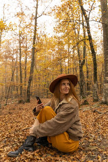 Portrait of fashionable redheaded young woman with cell phoine sitting in autumnal forest around - AFVF04886