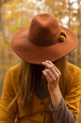 Fashionable redheaded young woman wearing felt hat in autumnal forest - AFVF04892