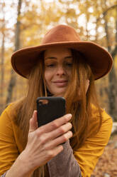 Portrait of smiling redheaded young woman in autumnal forest looking at cell phone - AFVF04895