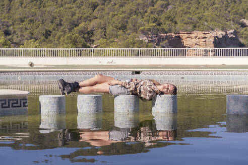 Young woman relaxing on bollards - AFVF04913