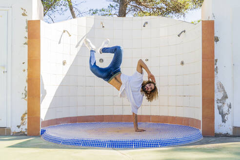 Portrait of young man doing handstand on one hand - AFVF04919