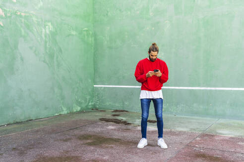 Young man wearing red sweatshirt raising hands in front of green wall - AFVF04922