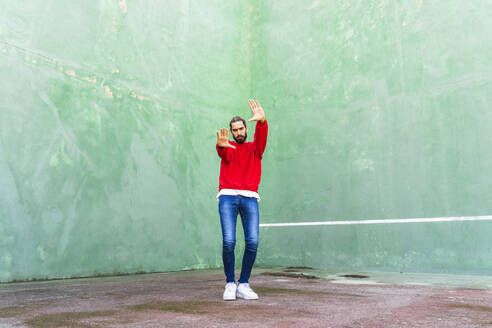 Portrait of serious young man wearing red sweatshirt raising hands in front of green wall - AFVF04925