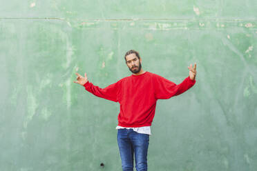 Portrait of angry young man wearing red sweatshirt in front of green wall - AFVF04931