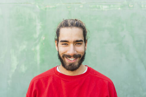 Portrait of bearded young man wearing red sweatshirt in front of green wall - AFVF04934