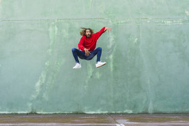 Portrait of young man in wearing red sweatshirt jumping in the air in front of green wall - AFVF04940
