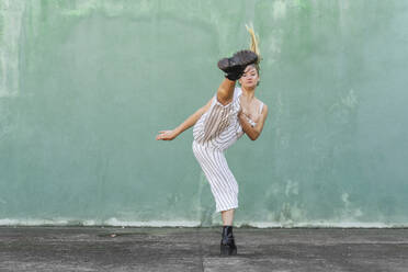 Young woman doing a high kick in front of green wall - AFVF04943