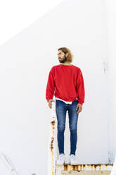 Portrait of bearded young man wearing red sweatshirt standing on rusty stairs - AFVF04946