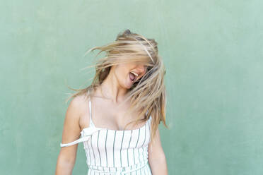 Blond young woman screaming and tossing her hair - AFVF04952