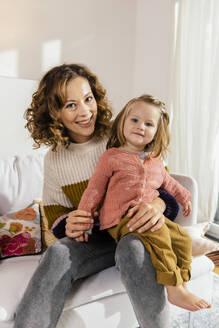 Portrait of happy mother with little daughter on couch at home - MFF04968