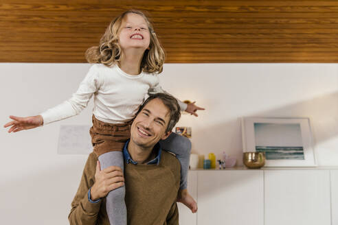 Happy father carrying daughter on shoulders at home - MFF04986