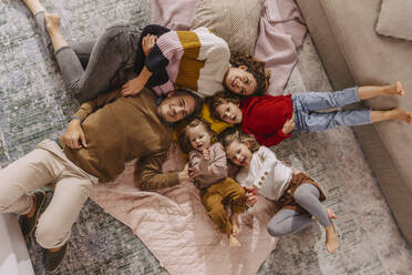 Happy family with three daughters lying on blankets at home - MFF04989