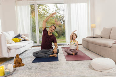 Father and daughter doing yoga together at home - MFF05013