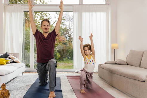 Father and daughter doing yoga together at home - MFF05016