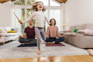 Exuberant girl with parents meditating at home - MFF05022