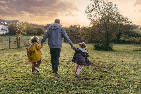 Father with daughters walking on a meadow in autumn - MFF05025