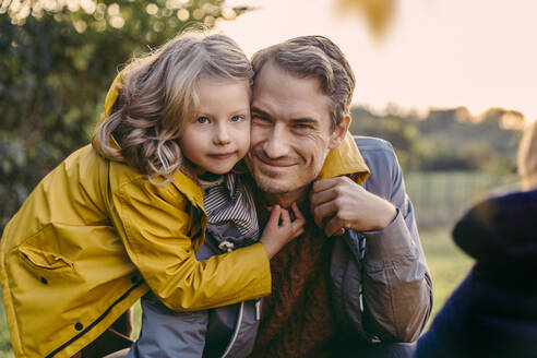 Portrait of girl hugging smiling father outdoors in autumn - MFF05031