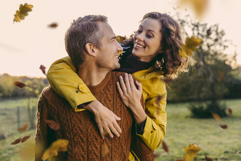 Man giving woman a piggyback ride outdoors in autumn - MFF05037