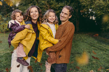 Portrait of happy family with two daughters outdoors in autumn - MFF05040