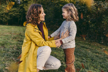 Smiling mother with daughter on a meadow in autumn - MFF05046
