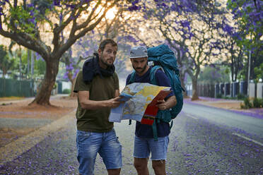 Backpackers with map on a street, Pretoria, South Africa - VEGF01267