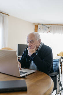 Portrait of senior man in wheelchair using laptop at home - JRFF03936