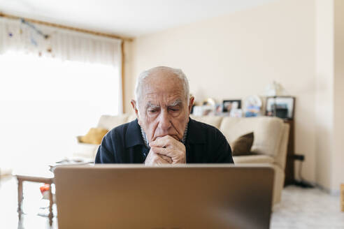 Portrait of senior man using laptop at home - JRFF03939