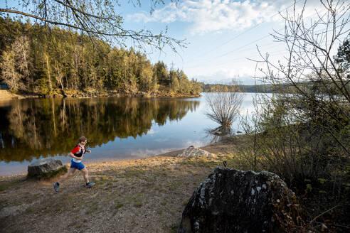Man running at the lakeside, Forstsee, Carinthia, Austria - DAWF01083