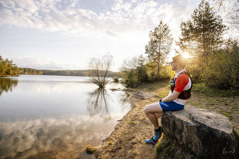 Sportive man sitting on a rock at the lakeside at sunset, Forstsee, Carinthia, Austria - DAWF01089