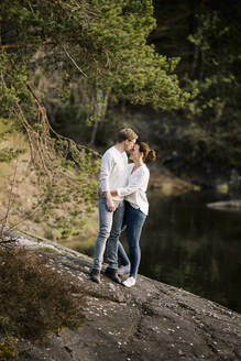 Affectionate couple standing on a rock at the lakeside, Forstsee, Carinthia, Austria - DAWF01095