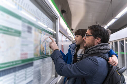 Father and daughter looking on map at metro station - ERRF02521