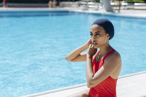 Portrait of young woman putting on swimming cap at poolside - SODF00449