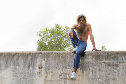 Young blond man sitting on a wall - AFVF04965