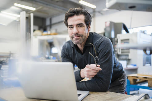 Portrait of businessman using laptop in a factory - DIGF09027