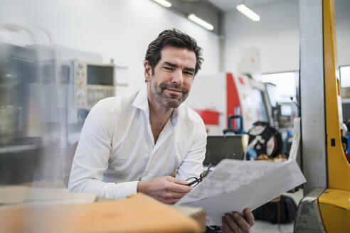 Portrait of a confident businessman with papers in a factory - DIGF09036