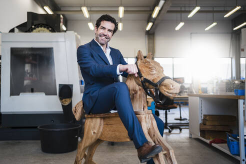 Portrait of a playful businessman on wooden rocking horse in a factory - DIGF09048