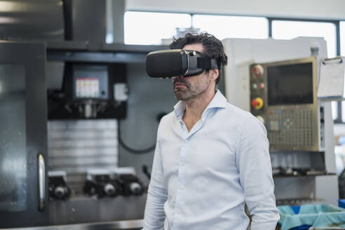 Businessman wearing VR glasses in a factory - DIGF09060