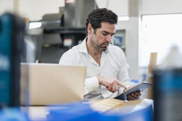 Businessman using tablet in a factory - DIGF09108