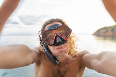 Young man with snorkel making a face on the beach - AFVF04979